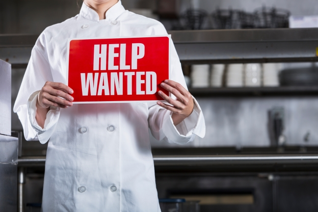 Female chef in restaurant kitchen, holding Help Wanted sign.